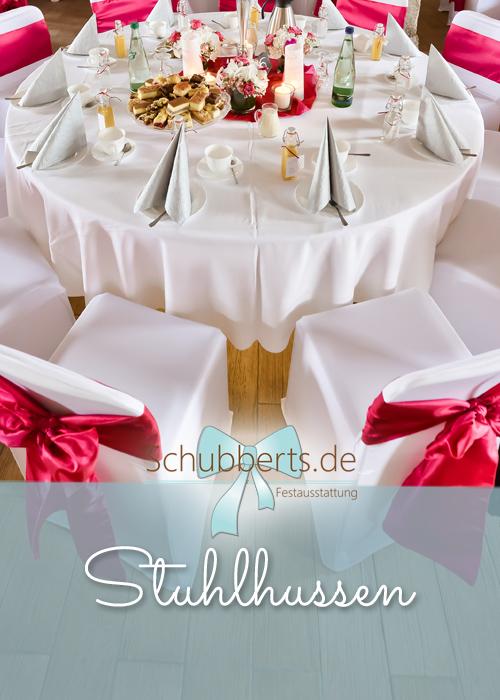 Hochzeitstafel mit Stuhlhussen und roten Stuhlschleifen