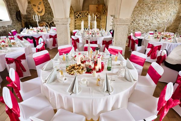 Tisch- und Stuhlhussen mit roter Satinschleife
